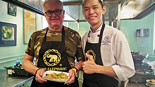 chef-and-studnent-holding-stir-fried-mushrooms-with-black-pepper-at-blue-elephant-cooking-school-in-bangkok-thailand